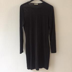 Sort kjole med glimmerdetalje og tyndt, gennemsigtigt stof på skuldre og ryg. Elastik bælte midt på ryggen. Går til midt på låret.  Style: Nalinih