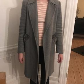 Fin uld 3/4 lang frakke i grå, med persianer på lommerne.  Str: S Farve: grå Materiale: 50% acryl, 30% polyester, 20% uld