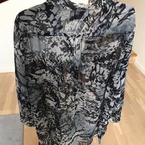 Carmakoma skjortekjole i gennemsigtig stof  med knapper og lommer ved brystet i str. XS. Brystmål: 130 cm
