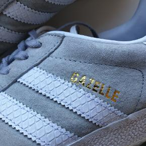 Adidas Gazelle i lysegrå ruskind.  Str. 40 2/3, måler 25,5 cm indvendigt.  Brugt, men stadig i god stand.  Ny pris 799 kr.
