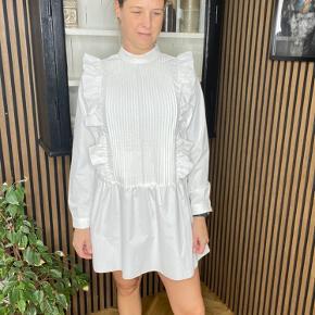 Smuk og meget elegant skjortekjole med store flæser og smock på brystet. Der er en knap i nakken og høj hals.