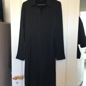 Flot meget mørkeblå kjole fra Cos. Materialet er 1% elastane og 99% viscose. Fin detalje ved ærmerne og slis bagtil. Måler cirka 110cm fra nakke og ned. Nypris 900