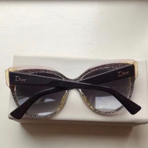 Dior solbriller i en mørk lilla/burgunder farge.