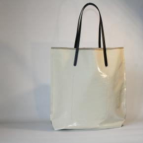 Smuk feminin shopper/totebag i lækker coated hør og i shiny cremehvid nuance. Fra det franske designbrand Jack Gomme.