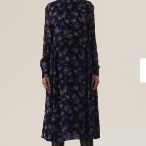 Maxi-kjole i transparent georgette med blomsterprint og høj hals. Løs pasform. Let og bølgende materiale uden stretch. Lynlås i ryggen. Med for. Modellen er 175 cm og bruger størrelse 36. Produkt ID: F3774.
