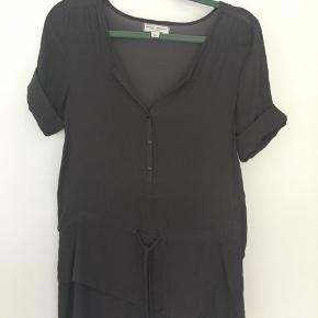 Grå skjorte med bindebånd. Den er kun brugt 2 gange, men der er en lille fejl på blusen (se billede 2).