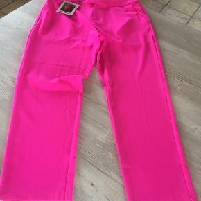 Helt nye bukser som lige er taget ud af den plomberet pose. Sælges til under halv pris  Custommade Adia Pants Pink Glo er de fedeste suitpants i en helt pink farve! De sidder utroligt godt og er lavet i et lækker og holdbart materiale. Foran er der to skrå lommer og bagpå er der en snydelomme. Lukkes med lynlås og hægter.