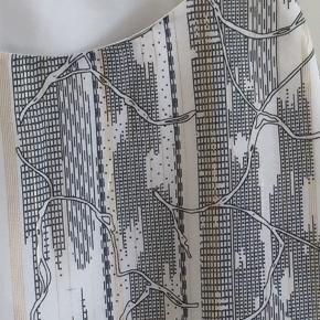 Foret top med smalle stropper. Mønster i sort, hvid og guld. Aldrig brugt.