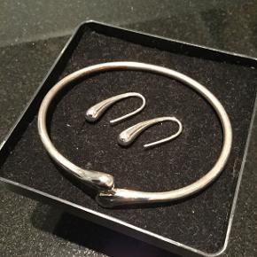 Enkelt smykkesæt i stramt design. Dråbeformede øreringe bærer sølvstemplet 925 for Sterling Sølv. Længe 2,7 cm. De står som nye. Armbånd i pletsølv. Diameter 7 cm. Armbåndet har lidt brugsslitage. Det er der taget højde for i prisen. Sættet er produceret af ukendt sølvsmed.