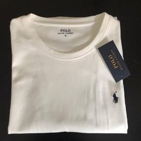 Sælger denne fede hvide t-shirt med rund hals fra Polo Ralph Lauren.  Tror umiddelbart jeg har købt herre modellen, men i en str. M og kan sagtens bruges af piger også, da ærmerne bare kan rulles lidt op :)  Helt ny, aldrig brugt stadig med mærket på.  Sendes med DAO via Trendsaleshandel - pris for fragt kommer oveni :)