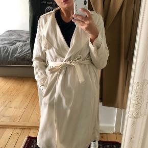 Massimo Dutti trench jakke. Polyester kvalitet, brugt et par gange, meget smuk og pæn at bære. Kan tages til rens og blive renset men er næsten lige blevet renset. Nyprisen da jeg købte i London var 2450kr, og står fin stadig.  Creme/hvid farve og ligner lidt satin/silke. Venlig respekter nyprisen og mindstepris på 650 kr. Sender gerne.