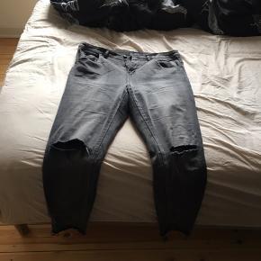 """Lysegrå jeans med huller ved knæene. På baglommen står der """"love not war"""". De er slimfit. Skriv gerne med flere spørgsmål."""