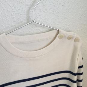 Lækker strik bluse, aldrig brugt. Vaskemærke mangler da det er en kollektions prøve. Stribet råhvid / navy Materialet er 50%uld 50%acryl Den skal vaskes på uld program og liggetørre. Længde 64 cm Brystvidde 46 cm Ærmelængde 60 cm