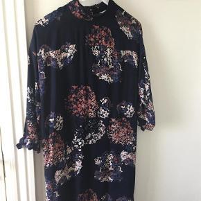 Varetype: Kjole Farve: Marine,råhvid og gylden Prisen angivet er inklusiv forsendelse.  Denne kjole er brugt til en konfirmstionsfest og få timer til en brunch. Den er helt som ny og sidder rigtig pænt. Lækker kvalitet som ikke krøller. Købt i maj måned 2017. Længden på kjolen er 95cm. Modellen hedder fleur dress.