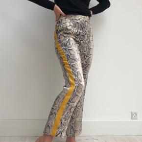 Fine bukser fra ZARA størrelse s. Slangeskindsmønster med gul stribe ned langs med benet. Skrålommer.