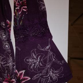 Tunika fra Cellbes, lilla med blomstermønster og dekorativ blondeindsats ved V-udskæringen og på de lange ærmer, der også har flæse i kanten. Model i A-facon af skøn jersey. Materiale: Modal Vask 40°. (Jeg har denne tunika til salg i både lilla og sort) Størrelse 50/52 Brystmål 136 cm Længde fra skulder 86 Evt. forsendelse er for købers regning.