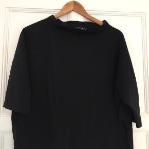 Fin bluse med høj og bred hals, der giver et stylish look.   Str. M