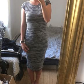 Lang kjole- kan sagtens brættes op uden den glider ned. Der er stræk i stoffet, så den sætter sig til kroppen 🙂