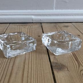 2 stk Holmegaard fyrfadsstager i glas Uden skår eller ridser Højde 2,5cm Pris er for begge   Fra hjem uden røg eller kæledyr.  Sender gerne, køber betaler porto. Kan også afhentes på Frederiksberg.