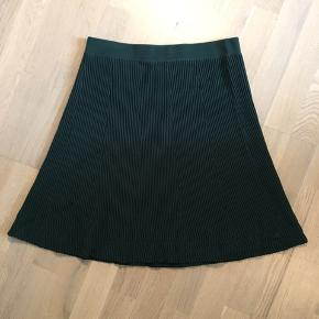 """Fejlkøb, derfor aldrig brugt. A-facon """"skater"""" nederdel i elastisk stof med """"strik"""" mønster. Mørk grøn."""