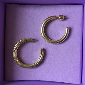 """2 stk. forgyldte hoop øreringe fra Maria Black.   Den til venstre er modellen """"ARSIIA 30 HOOP ØRERING"""" (nypris: 900 kr.) Den til højre er modellen: """"RUBY 28 HOOP ØRERING"""" (nypris: 600 kr.)   Begge er forgyldt 925 sterling sølv. Der er 2 mm. forskel på øreringenes størrelse (28 mm og 30 mm), men de kan sagtens bruges som et par, eller selvfølgelig enkeltvis.   Nypris samlet: 1500 kr.  Sælges samlet for: 500 kr."""