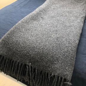 Brun plaid i uld. Tæppets farve er lidt mørkere end på billederne. Det måler 130 x 160 cm (+frynser). God stand - fra røg- og dyrefrit hjem.