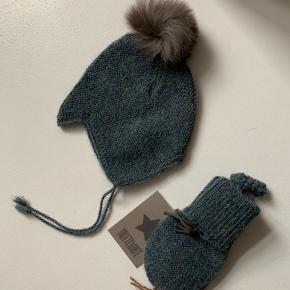 Huttelihut Bolivia vanter og hue med pels kvast, i alpaca uld. Str. 3-6 mdr. Sælges samlet for 400 kr. Aldrig brugt - stadig mærke i begge dele.  Nypris for hue: 400 kr. Nypris for vanter: 250 kr.
