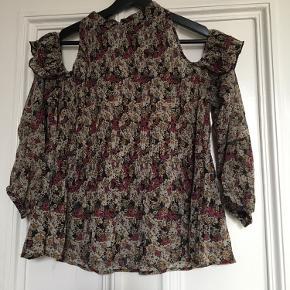 Smuk bluse med detalje ved skulder, der er hul så den hænger ned på skulder og sidder tæt i halsen