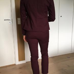 Virkelig flot sæt med habitjakke og bukser i bordeaux fra Neo Noir. Det er i rigtig pæn stand, kun brugt få gange.