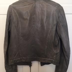 Lækker jakke fra Club Collection i lammeskind. Støvet grøn, str. M. Tegn på brug i form af patina, ellers meget velholdt. Kan sende med DAO, køber betaler fragt. Bytter ikke.
