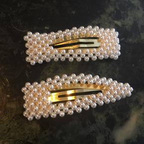 Populære hårspænder med små hvide perler.   Aldrig brugt. 40 kr. pr. stk. eller 75 kr. for begge to.   Jeg sender, eller vi kan mødes i Århus eller Kbh :)