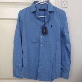 Helt ny Ralph Lauren dame skjorte i størrelse 8 (svarer ca til M). Købt i Harrods i London, og aldrig brugt! Stadig med mærke på, og ekstra knapper medfølger. Byd!