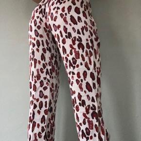 Mega bløde viskose bukser med lyserødt leopard print.   En tynd syning er løbet lidt bagpå - kan ses på billede 3. Det er ikke noget man lægger mærke til, når man har bukserne på. Ellers er de næsten som nye.   Str. er en 34/XS men passes nærmere af en 36/S  Sender med DAO. Køber betaler fragt. Bytter ikke.