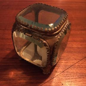 Super smukt gammelt skrin. Endnu et af dem fra slut 1800 start 1900.  Det mangler låsen (deraf prisen) men er ellers i god stand. Har spejl i bunden. Alt glas er intakt og messingen er også i fin stand.  Det har en god størrelse da det måler 11 cm i højden og 9 cm i længden.  Skal afhentes i lystrup eller sendes på købers regning.