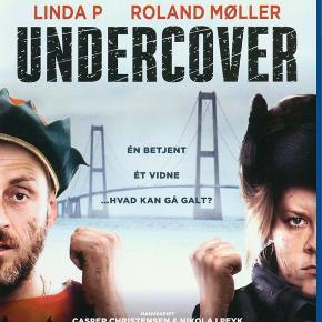 3230 - Undercover (Linda P) (Blu-ray) I FOLIE   Én betjent. Ét vidne. Hvad kan gå galt...?  Politibetjenten Rikke (Linda P) er besat af jul og glæder sig til andesteg og ris á la mande. Lillejuleaften tager hendes karriere dog en ny og overraskende drejning, da hun sendes ud på sin første undercover mission. Hun skal transportere småforbryderen og kronvidnet Mick (Roland Møller) til Fyn, inden den berygtede gangster boss Omar og hans håndlangere når at få fingre i ham og de 900.000 kr., han har stjålet. Meget mod sin vilje tager Rikke opgaven på sig og kører af sted med Mick på slæb. Med morderiske gangstere i hælene indser det umage par, at de må danne en højst usædvanlig alliance, hvis de skal slippe levende gennem julen.  Tekst fra omslag
