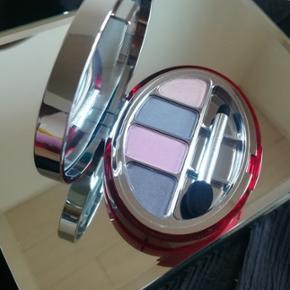 Ubrugt Clarins øjenskygge i flere violette, blå og grå nuancer 'Ocean'.Perfekt til gave da den kommer i rød blød pose.