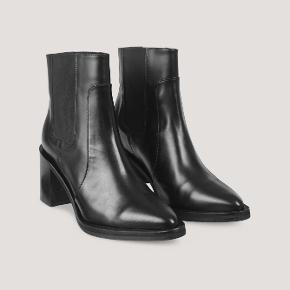 Smukkeste chelsea-støvler i fint læder med en raffineret poleret glans og elastik på siderne. Hæl højde er 7,5 cm. Brugt én gang, og de er derfor som nye. Nypris: 1600 kr. Skriv endelig for flere billeder.