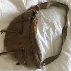 Rummelig Bum Bag, ruskind i en brunlig beige-grå nuance.   En skøn crossover med brugs-patina i et råt look og meget smuk farve. Ingen funktionsfejl.   Kom med et bud, jeg bytter helst ikke ✨