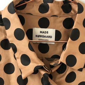 Funky prikket skjorte fra Mads Nørgaard sælges. Aldrig brugt. Farve: lys rust med sorte prikker. Materiale: 100 % bomuld.