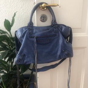 Balenciaga City taske i smuk blå farve. Misfarvet efter vandskade på bagsiden (derfor den billige pris) det kan slet ikke ses når man går med den da det udelukkende er på bagsiden. Crossbody rem medfølger. Kvit haves ikke. Fast pris.