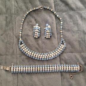 Smykkerne har jeg arvet efter min mormor, som fik dem som gave fra Amerika i 50'erne. Armbåndet måler 19 cm når det er på. Kæden måler 37 cm, og runder, så det lægger sig smukt om halsen halsen, som det det blevbrugt i 50'erne. Betaling med Mobilpay  halskæde armbånd ørenringe (selvfølgelig clips) Farve: sarte pastelfarver