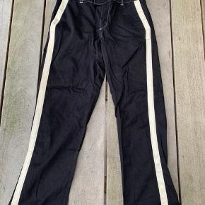 Spillende bukser i sorte med hvid stribe løbende på hver side. Str m. Brugt meget få gange.  Betaling foregår via tradono eller på mobilepay.