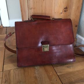 Brun lædertaske med læderstrop. Købt i Amsterdam for 3 år siden og aldrig brugt. Størrelse: normal computertaske størrelse