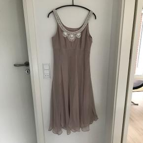 Gudesmuk silkekjole i rosa/pudderfarve med håndsyede perler. Købt i London (nypris kr 3000) Har været brugt 3 gange. Stoffet har en lille plet foran, men har ikke været forsøgt renset. En eksklusiv og helt fantastisk kjole. Bytter ikke.