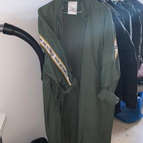 Army-grøn jakke/frakke fra Won Hundred. Den kan passes af en S-L afhængigt af hvor oversize du vil have den skal sidde.  Jeg har købt den herinde, men synes desværre den er lidt stor til mig.   To små huller ved lommen.