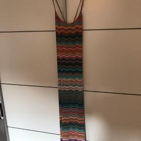 Aldrig brugt!  Fin lang kjole i flot mønster og med flot udskæring som smyger sig ind til kroppen. Med stræk, så kan passes af de fleste. Silkeagtigt stof.  Købt i en fin kjolebutik på Kreta.