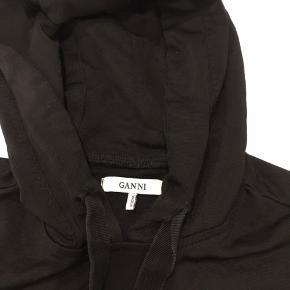 Ganni hoodie med blonde detaljer . I fin stand . Der er en lille tråd udtrækning  på det ene ærme . Den er helt sort . Ikke falmet som billedet viser da det er taget i aften belysning . Rigtig fin bluse.
