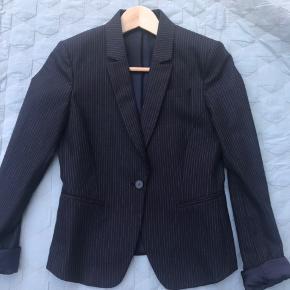 Klassisk smuk jakker fra Tiger som sidder utroligt flot. Men jeg får desværre brugt den alt for lidt. Den er et år gammel og ny pris var over 3000 kr. Den er mørke blå, str 34 og fejler ingen ting. Fra ikke-ryger-hjem. Sender gerne med dao. Bytter ikke. Kom gerne med bud.