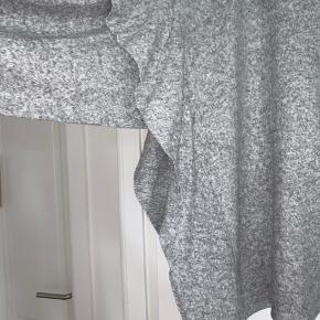 Grå fleece trøje med flagre ærmer.