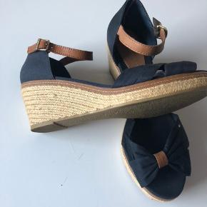 Flotte sandaler med kilehæl i mørkeblå. Aldrig brugt. Nypris kr. 800,- Sælges for kr. 400,- + Porto eller afhentet Odense S